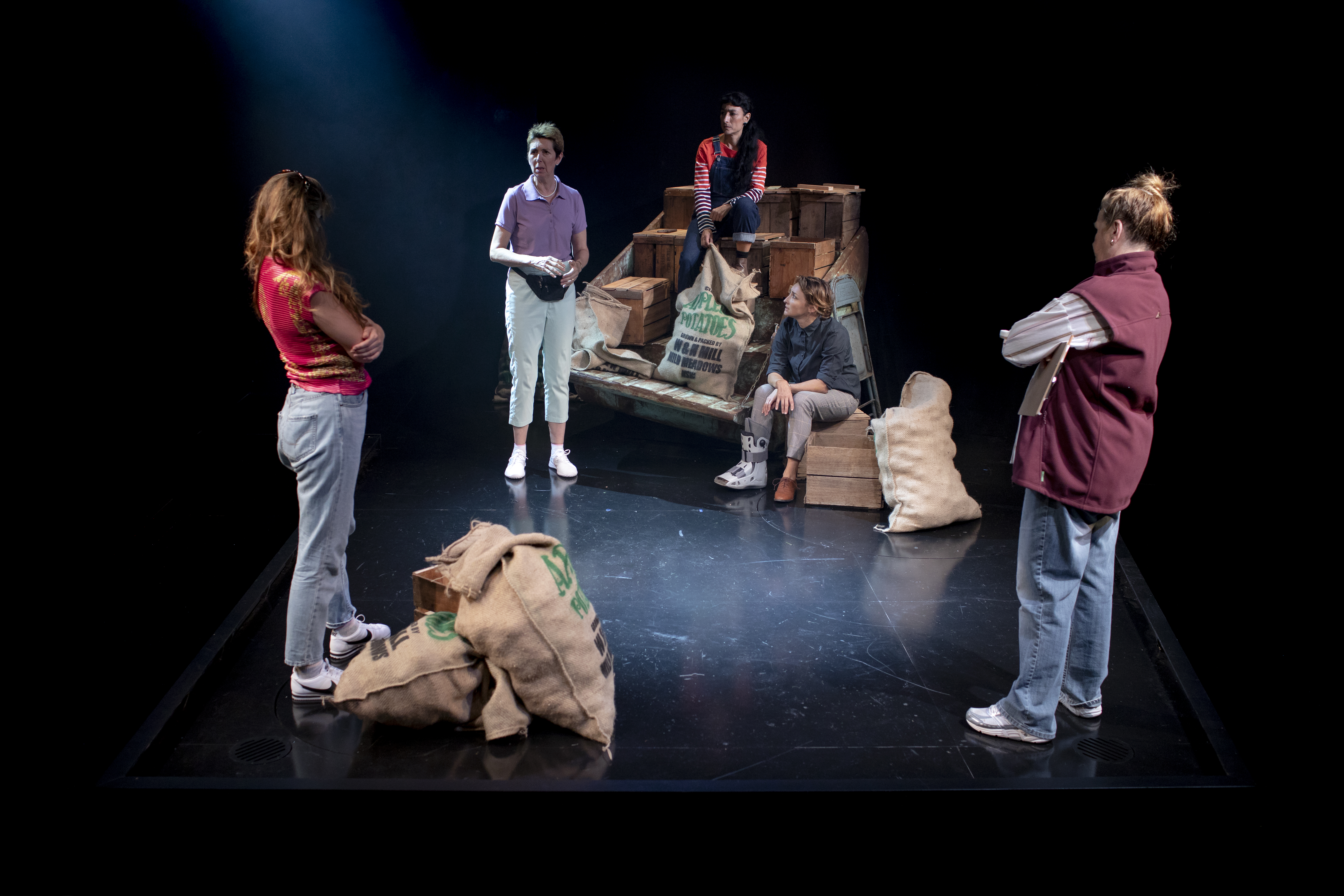 A group of women actors stand on a stage set made up of sacks of potatoes and tiered rows of crates. Two actors in the foreground both wearing jeans and red tops have their backs to the camera. The other three actors face the camera. One stands and is wearing a purple shirt, green pants, white runners and a black bumbag. The others are seated, One has her foot in a moon boot. The ther wears blue overalls and a striped red top. It looks like they are deep in conversation.
