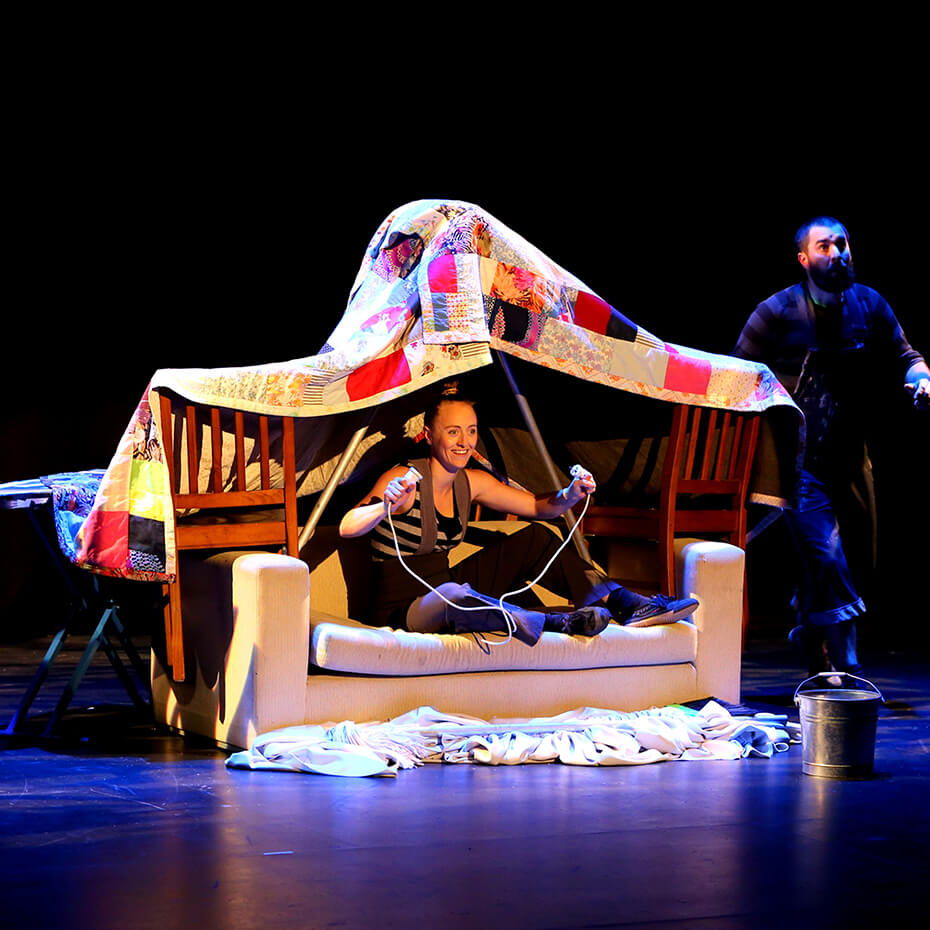 two performers building fort on sofa
