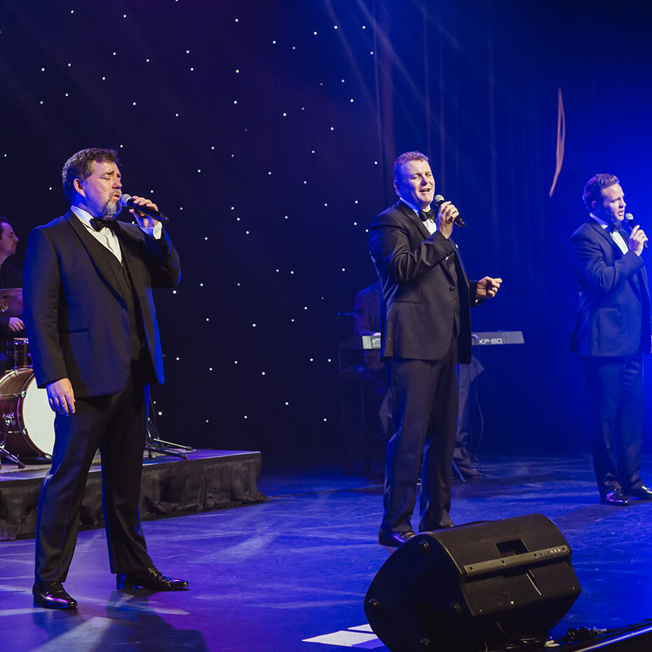 three men singing on stage