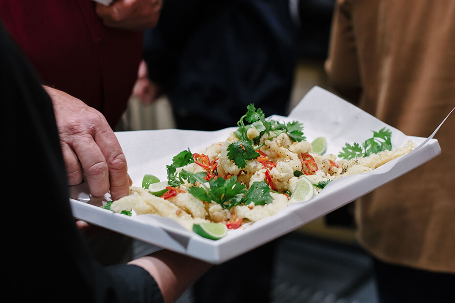 Platter of food being offered with hands taking food
