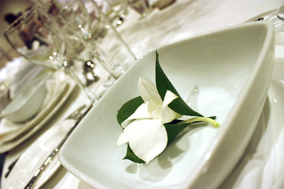 White flower in bowl on table set for wedding