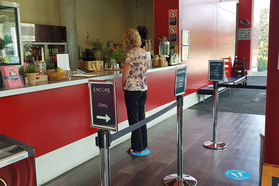 Lady standing in line on social distance dot at cafe